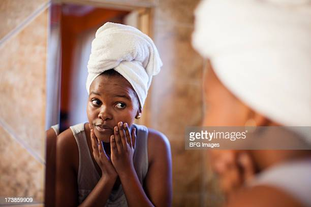 Young woman checking her skin in the mirror. Cape Town, Western Cape Province, South Africa