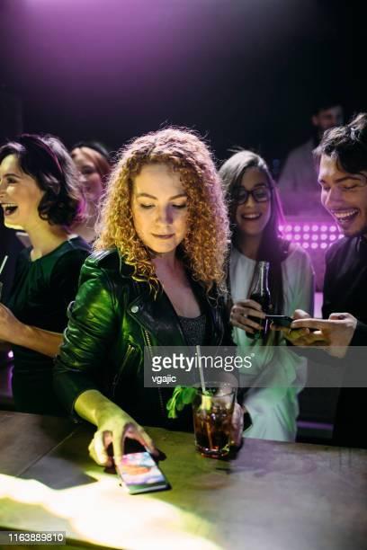 ナイトクラブで彼女のスマートフォンをチェックする若い女性 - クラブdj ストックフォトと画像