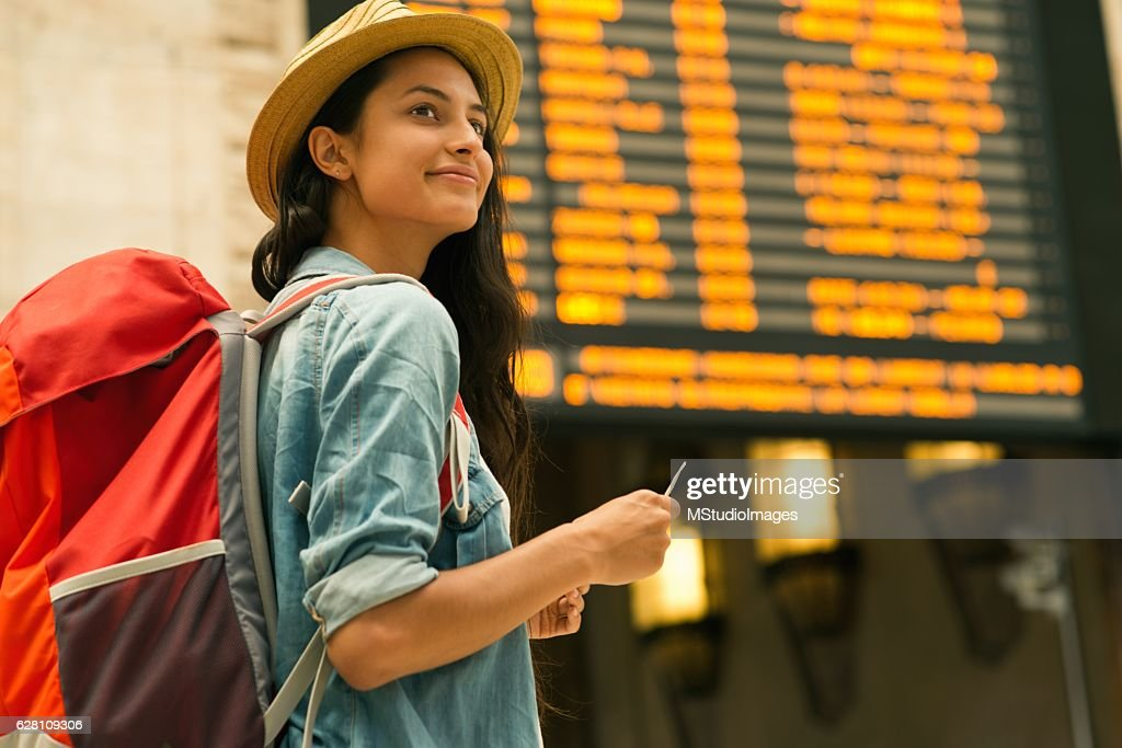 Young woman checking her train in time board : Stock Photo