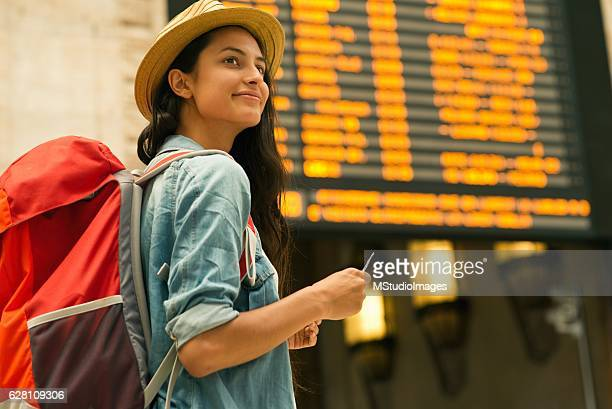 young woman checking her train in time board - rucksacktourist stock-fotos und bilder