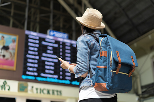 Young woman checking her train in timetable board - gettyimageskorea