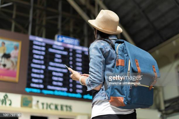 young woman checking her train in timetable board - travel destinations stock-fotos und bilder