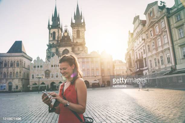 young woman checking mobile in front of tyn church in prague - czech republic stock pictures, royalty-free photos & images
