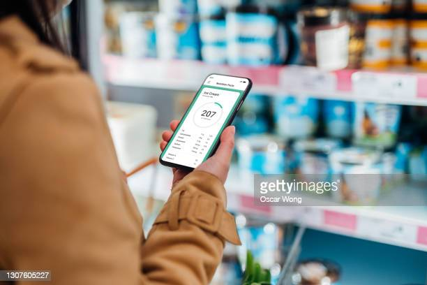 young woman checking nutrition and calories intake on smartphone while shopping in supermarket - supermarket stock pictures, royalty-free photos & images