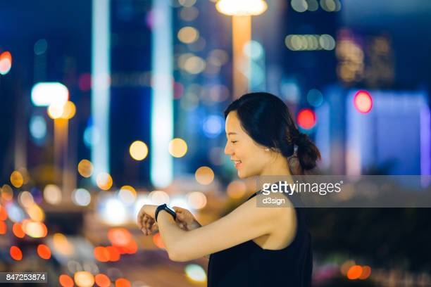 Young woman checking on her smart watch outdoors against urban city skyline at night