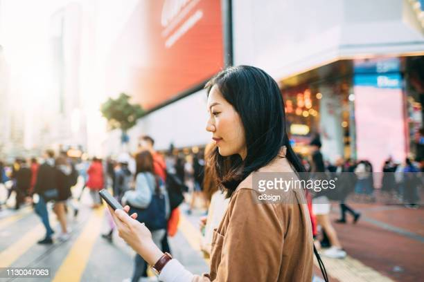 young woman checking on mobile phone while crossing street and commuting in busy downtown city street - pedestrian stock pictures, royalty-free photos & images