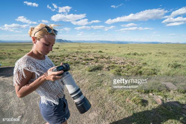 Young woman checking picture after safari