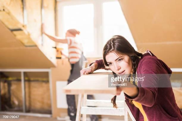 young woman checking plank on construction site - renovierung konzepte stock-fotos und bilder