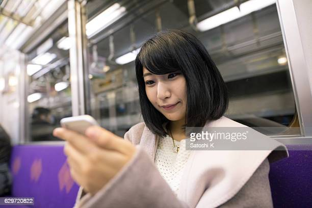 Young woman checking screen on smart phone in train