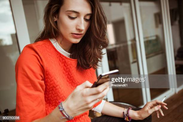 young woman checking smartphone on balcony smoking a cigarette - beautiful women smoking cigarettes stock pictures, royalty-free photos & images