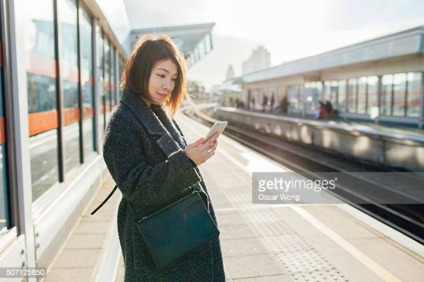 Young woman checking smartphone on the train platform