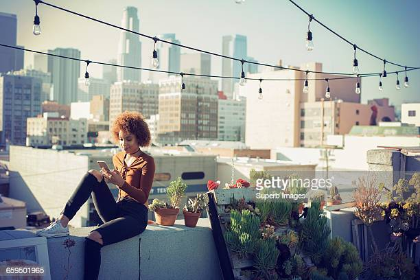 young woman checking smartphone on urban rooftop - afro amerikaanse etniciteit stockfoto's en -beelden