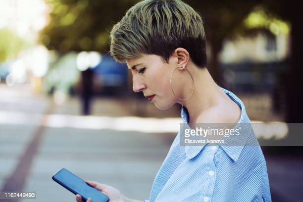 young woman checking social media - non binary gender stock pictures, royalty-free photos & images