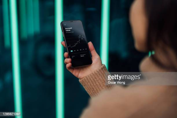 young woman checking stock market data on smartphone - bank stock pictures, royalty-free photos & images