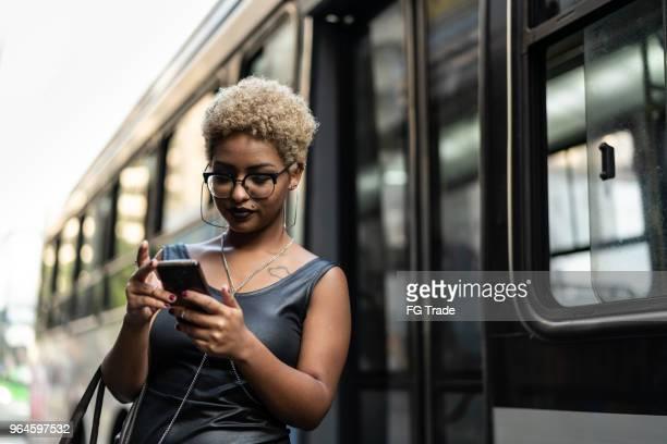mulher jovem, verificar o tempo de embarque para ônibus - esperar - fotografias e filmes do acervo