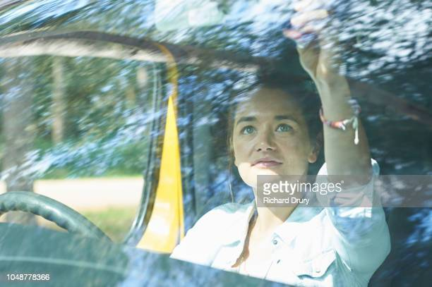 Young woman checking the rear view mirror of her camper van