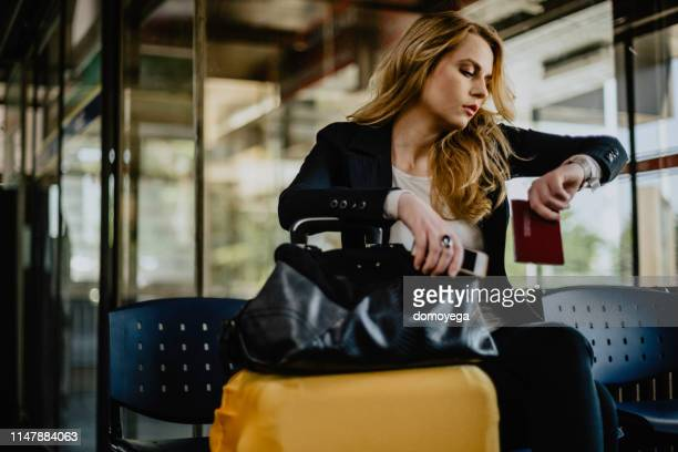 young woman checking the time and waiting at the airport - waiting stock pictures, royalty-free photos & images