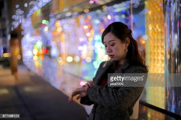 若い女性のクリスマスの照明を通り decolatd で時間をチェック