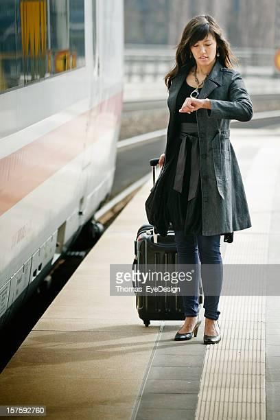 Junge Frau, die Zeit auf einen Zug Plattform