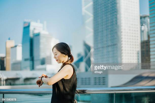 Young woman checking time on smart watch in financial district in city