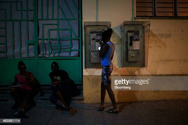 A young woman checks a mobile phone while talking on a public phone in Santiago de Cuba Cuba on Tuesday Jan 6 2015 US companies will be permitted to...