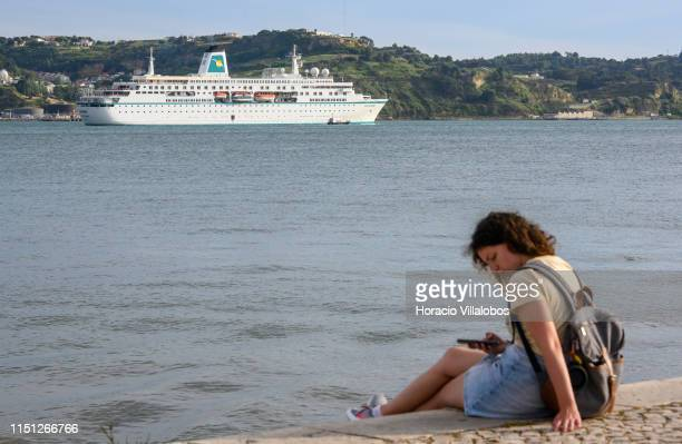 A young woman checks her cellphone sitting by the riverside as MS Deutschland a cruise ship registered in Nassau Bahamas sails on the Tagus River...