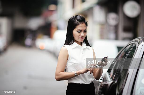 A young woman checks her phone in front of her car