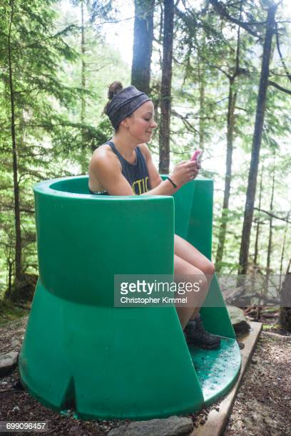 A young woman checks her phone while using an open air outhouse located in the forest near a campsite in Bowron Lake Provincial Park.
