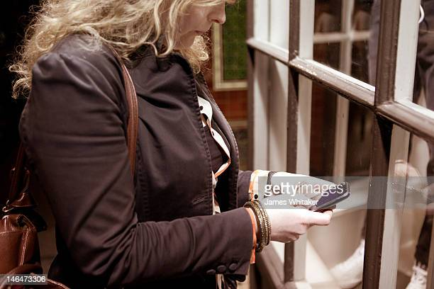 Young Woman checks phone by shop window