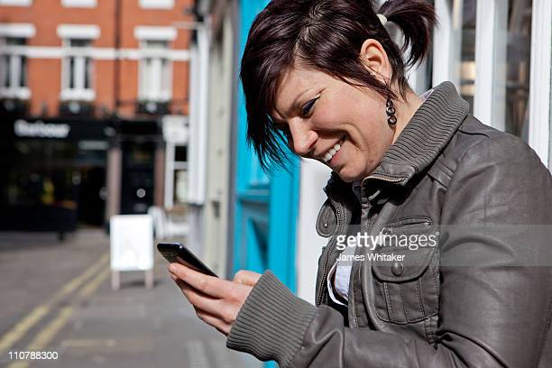 Young Woman checks phone in London Street