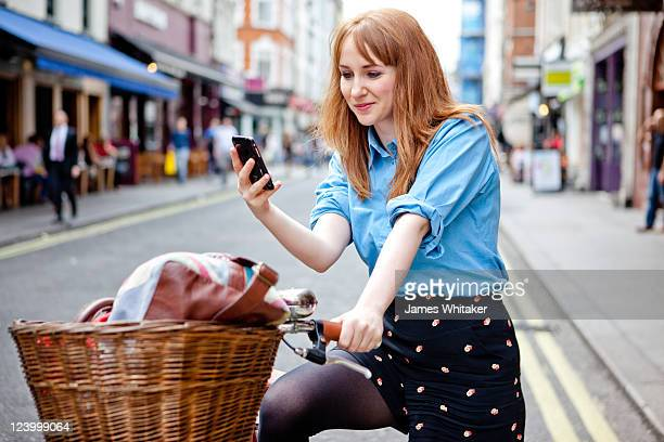 Young woman checks phone on bike