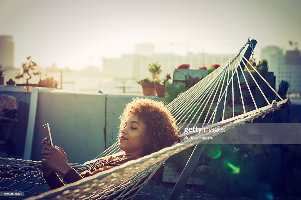 Young woman checks smartphone from hammock