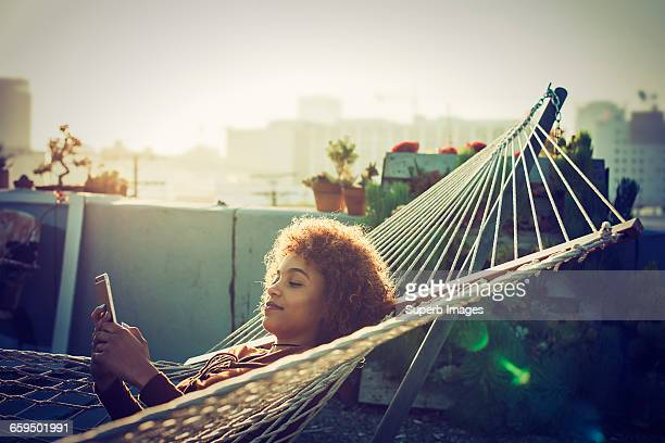 young woman checks smartphone from hammock - hamac photos et images de collection