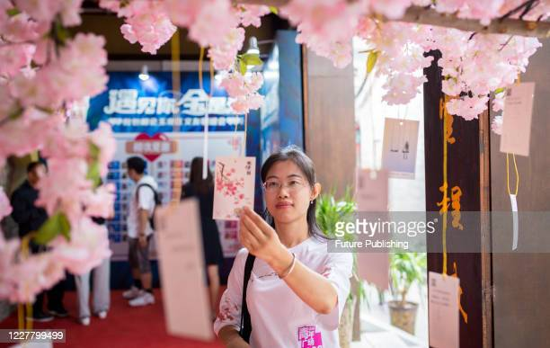 HOHHOT CHINA JULY 25 2020 A young woman checks the fate card information at a blind date party Hohhot Inner Mongolia China July 25 2020 PHOTOGRAPH BY...