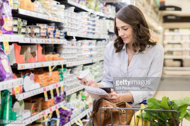 Young woman checks yogurt ingredients while grocery shopping