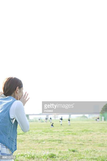 Young woman cheering on field