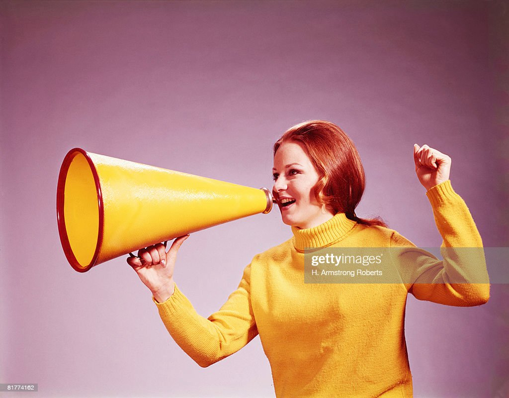Young woman cheerleader in yellow turtleneck sweater, yelling into yellow megaphone. (Photo by H. Armstrong Roberts/Retrofile/Getty Images) : Foto de stock