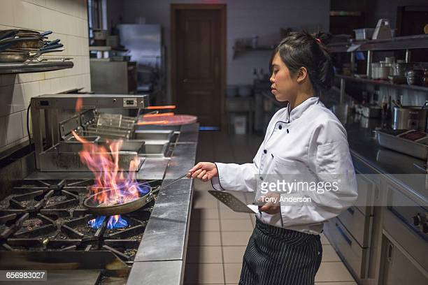 Young woman chef in restaurant kitchen