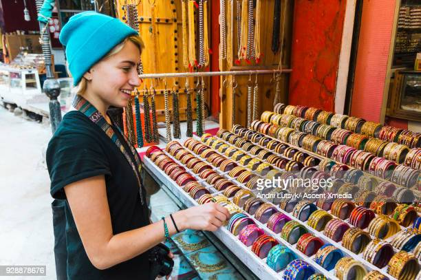 Young woman chooses bracelet in market