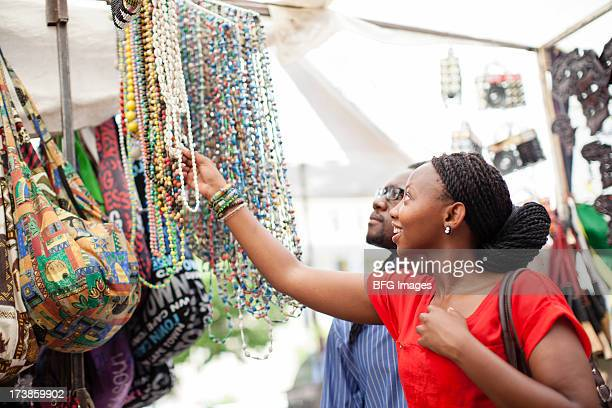 Young woman choosing a beaded necklace at an African Market. Cape Town, Western Cape Province, South Africa