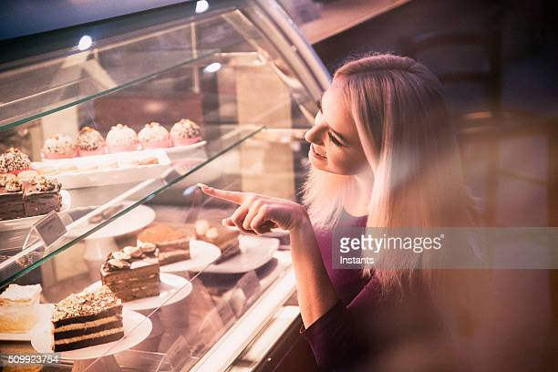 Young woman choosing a pastry in a bakery