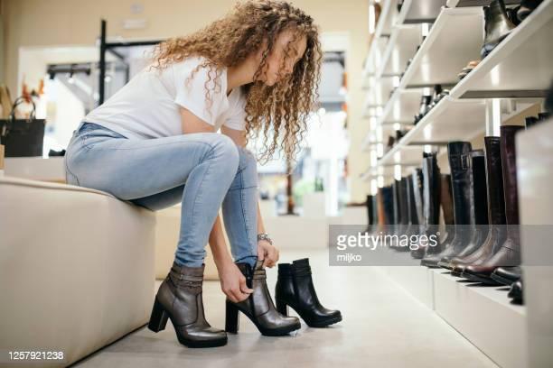 若い女性がブティックで靴を選んで買う。 - ブーティ ストックフォトと画像