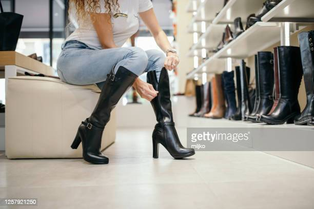 young woman choosing and buying shoes in boutique. - scarpe foto e immagini stock