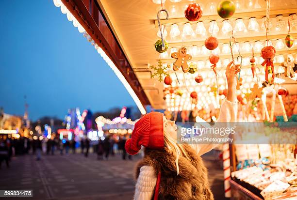 Young woman choosing baubles at xmas festival in Hyde Park, London, UK