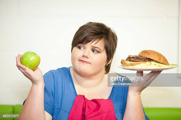 young woman choosing between an apple and a burger - grasa nutriente fotografías e imágenes de stock