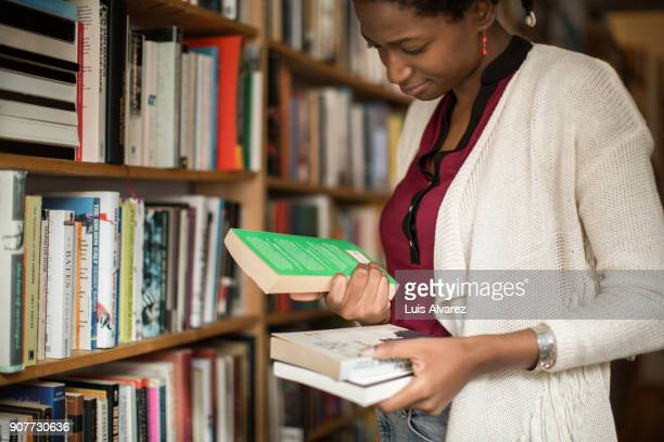 Young woman choosing books at bookstore
