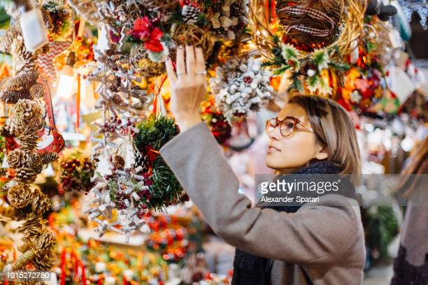 young woman choosing christmas decoration on a christmas market in barcelona, spain - christmas market stock pictures, royalty-free photos & images