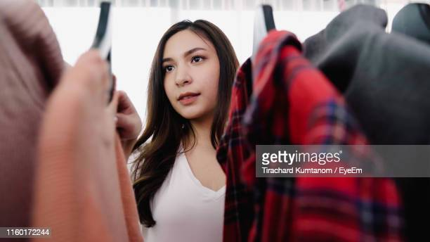 young woman choosing clothes from closet - closet stock pictures, royalty-free photos & images