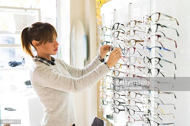 Young woman choosing glasses in optical shop