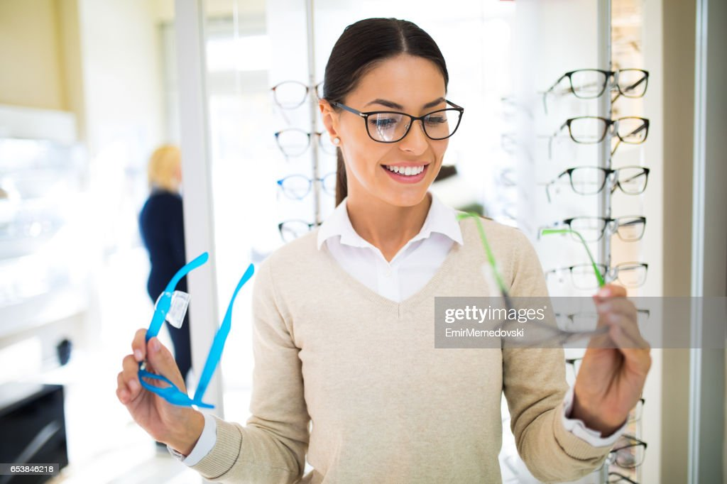 Young woman choosing glasses in optical shop : Stock Photo